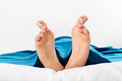 Female feet with stretched thumbs with smiley and grumpy drawn on them. A close-up shot of female feet with stretched thumbs with smiley and grumpy drawn on them Stock Image