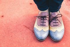 Female feet in stylish shoes brogues on brown surface. Female feet in stylish shoes brogues lace standing together on a brown surface Royalty Free Stock Photo