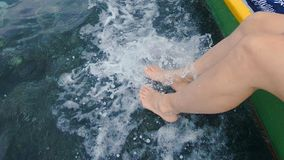 Female Feet Surfing. Young Woman Playing With The Surf With Her Feet, Dangling Her Legs From A Moving Fishing Boat Onto The Water Surface Of The Clear Tropical royalty free stock photos