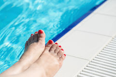 Female feet at swimming pool side Stock Image