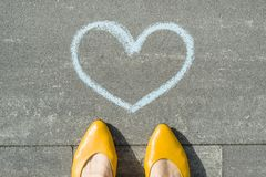 Female feet with symbol of the blue heart painted on the asphalt.  stock image