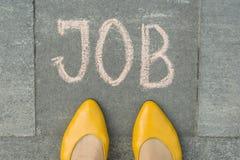 Female feet with text job written on grey sidewalk stock photo