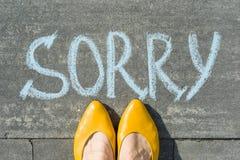 Female feet with text sorry written on asphalt. Female feet with text sorry written on asphalt stock photos