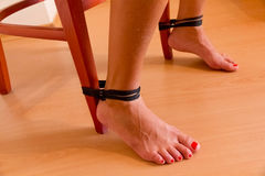 Female feet tied to chair. Female feet tied to a chair against wooden floor Royalty Free Stock Photos
