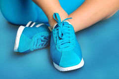 Female feet in turquoise sneakers on turquoise sports mat Royalty Free Stock Photography