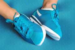 Female feet in turquoise sneakers on turquoise sports mat. Stock Photo