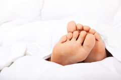 Female feet under bed sheet Stock Photos