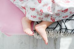 Female feet under blanket flat lay. Beautiful legs of the little girl feet with red pedicure on the bed. royalty free stock photography