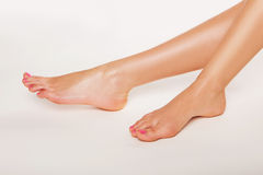 Female feet with varnished toenails. Tanned bare female feet with varnished toenails on a white background conceptual of podiatry, beauty, glamour , hygiene and Stock Images