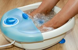 Female feet in a vibrating foot massager. Electric massage foot bath. Relax after work.  Royalty Free Stock Image