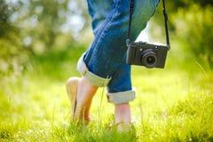 Female Feet and vintage retro photo camera outdoor Royalty Free Stock Photo