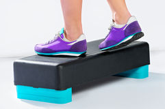 Female feet in violet sneakers do exercise on aerobic step. Royalty Free Stock Photography