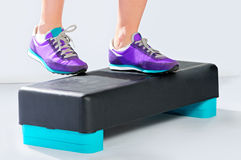 Female feet in violet sneakers on fitness aerobic step. Female feet in violet sneakers do exercise on a black-turquoise fitness aerobic step. Side view Stock Image