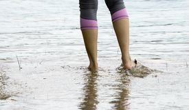 Female feet while walking in a beach. Waters stock images