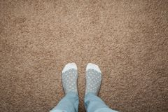 Female feet in warm socks against a background of brown carpet, space for text.  stock photo