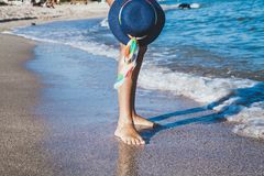Female feet on the sea beach. Female feet in waves of the sea and hat on summer sunny beach Royalty Free Stock Photo