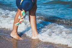 Female feet on the sea beach. Female feet in waves of the sea and hat on summer sunny beach Stock Images