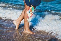 Female feet on the sea beach. Female feet in waves of the sea and hat on summer sunny beach Stock Photo
