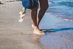 Female feet on the sea beach. Female feet in waves of the sea and hat on summer sunny beach Royalty Free Stock Images