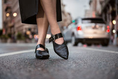 Female feet wear elegant leather shoes. Woman feet wearing high-heels on city street Royalty Free Stock Photos