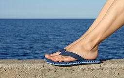 Female feet wearing blue flip-flops royalty free stock image