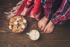 Female Feet Wearing Cozy Warm Pajamas Pants Jar with Gingerbread Cookies Cup of Hot Cococa with Marshmellow Cozy Christmas Concept. Above Top View Toned Wooden royalty free stock images