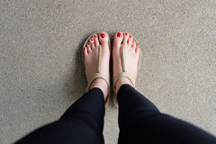 Female feet wearing slippers or flip-flop outdoor red nail Royalty Free Stock Images