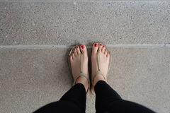 Female feet wearing slippers or flip-flop outdoor red nail Royalty Free Stock Image