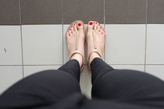 Female feet wearing slippers or flip-flop outdoor red nail Stock Photo