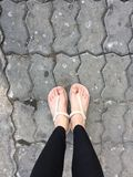 Female Feet Wearing Slippers on Tile Background Stock Images