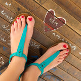 Female feet wearing turquoise sandals. Royalty Free Stock Images