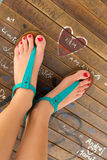 Female feet wearing turquoise sandals. Stock Images