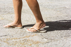 Female feet wearing white flip-flops. Female feet in white flip-flops with rock in the background Stock Photography