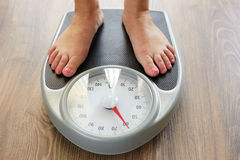 Female feet with weight scale. Female bare feet with weight scale on the wooden floor Stock Photos
