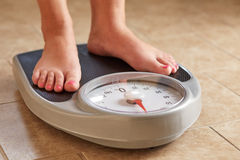 Female feet on weight scale. A pair of female feet on a bathroom scale Stock Photos