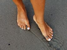 Female feet on the wet beach sand Royalty Free Stock Images