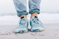 Female feet in wet jeans and sneakers. On the beach close-up Royalty Free Stock Photo