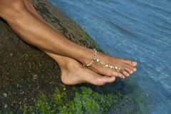 Female feet on wet stone and bracelet on ankle Stock Image