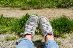 Female feet in white canvas sneakers and blue jeans in a grass Royalty Free Stock Photos