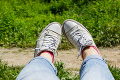 Female feet in white canvas sneakers and blue jeans in a grass. By the dirt path Royalty Free Stock Photos