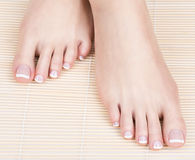 Female feet with white french pedicure on nails. at spa salon Royalty Free Stock Photos
