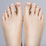 Female feet with white french pedicure on nails. at spa salon Royalty Free Stock Image
