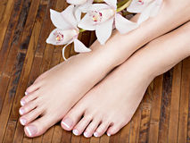 Female feet with white french pedicure on nails. at spa salon Stock Photos