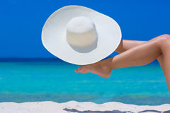 Female feet and white hat on the beach. Blue sea and sky background stock images