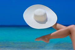 Female feet and white hat on the beach. Blue sea and sky background royalty free stock image