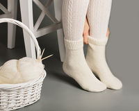 Female feet in white knitted stockings and socks near the basket Royalty Free Stock Photo