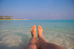 Female feet on white sandy beach and clear water Stock Images