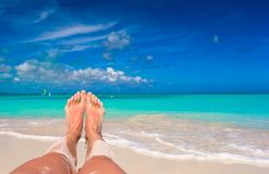 Female feet on white sandy beach Stock Photos
