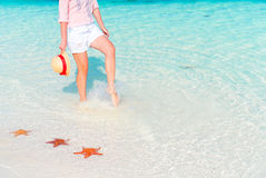 Female feet on white sandy beach. Starfish on the white sand beach in shallow water Royalty Free Stock Image
