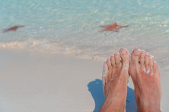 Female feet on white sandy beach. Starfish on the white sand beach in shallow water Stock Photo
